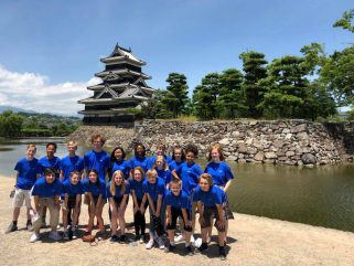 Students stand in front of Japanese castle.